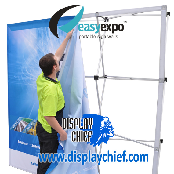 Man putting up sign onto the Easy Expo Display Chief pop up banner sign wall display system